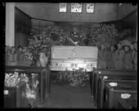 Charles H. Crawford's coffin lying in church with flowers and Boy Scouts standing on each side in Los Angeles, Calif., 1931