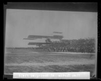 Copy of photograph of Glen Curtiss flying a few feet above ground in front of crowd at Dominguez Field