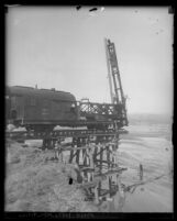 Workers on railcar installing supports for bridge being built across Santa Clara River Valley flood plain after St. Francis Dam disaster (Calif.), 1928