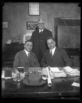Chief of Police James E. Davis sitting at desk with commissioner Birnbaum and Deputy Chief Cleveland Heath