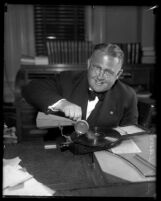 Los Angeles judge Leroy Dawson seated at desk playing with a portable phonograph, circa 1931