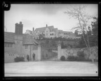 View of front gates, hillside, and Greystone Mansion on top of hill in Beverly Hills, Calif., 1929