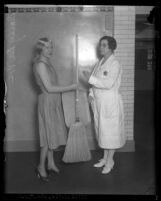Clara Bow's former assistant, Daisy De Voe, wearing apron & holding a broom poses with jail matron Vada Sullivan