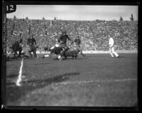 Football Iowa defenders tackling a U.S.C. back at the Coliseum in 1925