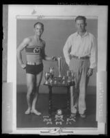 Junior Olympian Tony Galasso and his coach Ted Burns posing with trophies, Los Angeles, Calif., 1928
