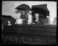 Los Angeles judge Carlos Hardy and two others in courtroom holding umbrellas over their heads, circa 1920