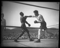 Boxer Tiger Flowers deflecting a blow from Eddie Huffman in Los Angeles, Calif., 1926