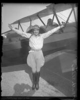 Aviatrix Ruth Elder with arms out stretched in front of her plane, Calif. circa 1927