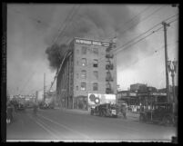 Firefighters on ladder fighting fire on 5th floor of Newmark Bros. building in Los Angeles, Calif., 1928
