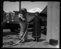 Minnie Kennedy doing radio interview with deep-sea diver R.C. Crawford during search for McPherson's body in Santa Monica, Calif., 1926