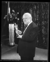Founder and president of Universal Pictures, Carl Laemmle holding an Oscar trophy, 1930