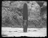 Surfer and Olympic swimmer Duke Kahanamoku standing on beach with surfboard in Los Angeles, Calif., circa 1920