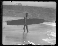 Surfer and Olympic swimmer Duke Kahanamoku walking on shoreline with surfboard in Los Angeles, Calif., circa 1920