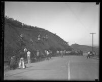 Workermen removing loose rocks from embankment along Laurel Canyon Road