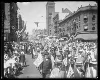 Street packed with spectators and marchers carrying American flags during Preparedness Day Parade in Los Angeles, Calif., 1916