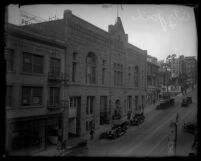City street with pedestrians, cars and buildings including Los Angeles city jail, circa 1920