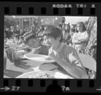 Howard Tsang and others competing in chow mein eating contest in Los Angeles' Chinatown, 1973