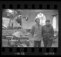 Reverend Troy Perry and Jerry Small standing amid fire damage at Metropolitan Community Church in Los Angeles, Calif., 1973