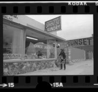 Hong Wah Chinese Laundry, Jick Hong Wong sweeping up pieces of window shattered by earthquake in Ventura, Calif., 1973