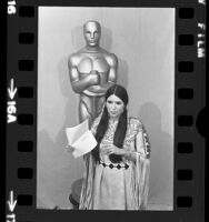 Sacheen Littlefeather standing before Oscar statue holding Marlon Brando's statement at the 45th annual Academy Awards in Los Angeles, Calif., 1973