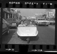 "Steven Goldsmith and Rich Blum driving their ""People Powered Vehicle,"" pedal car down Fairfax Avenue in Los Angeles, Calif., 1973"