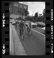 Councilman Marvin Braude bicycling to work with Claire Rogger, and Bob Reiter, passing the Sheraton West building in Los Angeles, Calif., 1974