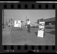 "Kaz Hirata standing outside his gas station with ""No Gas"" signs written in English and Chinese in Los Angeles' Chinatown, Calif., 1974"