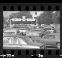 Lines of automobiles waiting at car wash-gas station during oil crisis in Los Angeles, Calif., 1974