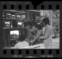Women with children watching Senate Watergate Hearings on televisions in a Sears department store in Los Angeles, Calif., 1973