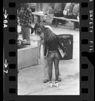 Female student dressed in cut-off jean shorts, tights and platform shoes talking with classmate at Hamilton High School in Los Angeles, Calif., 1973