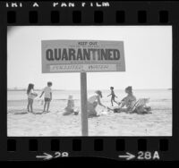 """Quarantined…Polluted Water"" sign with children playing in sand behind it on Cabrillo Beach, Calif., 1973"