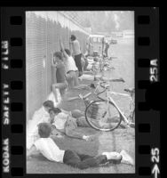 Youngsters and adults watching through chain-link fence at Los Angeles Rams training camp in Fullerton, Calif., 1973