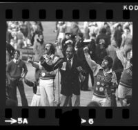Los Angeles Mayor Tom Bradley cheering with UCLA Bruins cheerleaders during game against USC, 1973