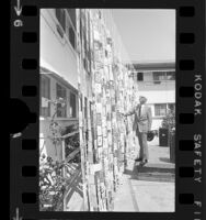 """Harold M. S. Richards of """"Voice of Prophecy"""" radio broadcasts viewing wall of birthday cards in Glendale, Calif., 1973"""
