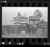 "Sign, over looking horse corral, with woman in bathing suit and reading ""Hey Look Me Over GO Army Reserve"" Pomona, Calif., 1973"