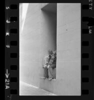 Male runaway sitting in alcove of building in Los Angeles, Calif., 1973