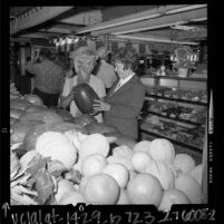 Two women inspecting melons at the Farmer's Market in Los Angeles, Calif., 1972