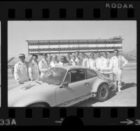 Group portrait of race car drivers around Porsche Carrera at Riverside International Raceway, Riverside, Calif., 1973