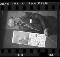 R.C. Baumgartner, chairman of Ridge Tool Company posing with company's pin-up calendar, 1973