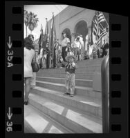 Daryle Klein, 3, waving flag as color guard stands on steps of city hall during POW/MIA demonstration in Los Angeles, Calif., 1973