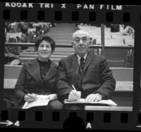 Chuck and Jean Weinstock, sports statisticians seated courtside in Los Angeles, Calif., 1973