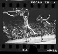 UCLA basketball player Bill Walton leaping for rebound in game vs Notre Dame, 1974