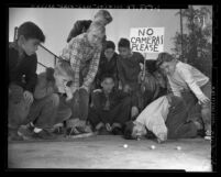 "Boys playing in marbles tournament, one with sign reading ""No Cameras Please,"" 1950"