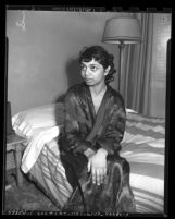 Assault victim Nydia Brisson seated on bed in boardinghouse at 259 E. 41st Place in Los Angeles, Calif., circa 1950