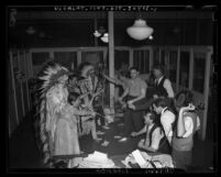 Behind the scenes at 1939 Union Station Pageant people dressed as Native American Indians holding up men in business office