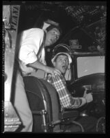 Comedians Dean Martin and Jerry Lewis mugging it up in cockpit of airplane, circa 1950