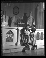 Two girls praying at alter of Daughters of Charity orphanage in Los Angeles, Calif., 1950