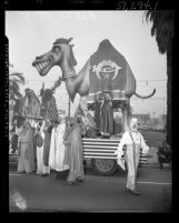 Shriners dressed in Arab robes with float in shape of a camel during Shriners convention parade in Los Angeles, Calif., 1950