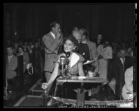 Dorothy Healey at microphone during city council debate on requiring Communists to register Los Angeles, 1950