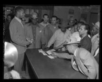 Douglas F. Shaw accepting badges of resigning reserve police officers at Newton Street Station after death of James Woodson Henry, Los Angeles, Calif., 1950